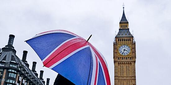Женщина держит зонт с флагом Великобритании