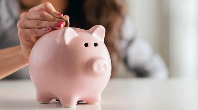 Женщина опускает монету в свинью-копилку