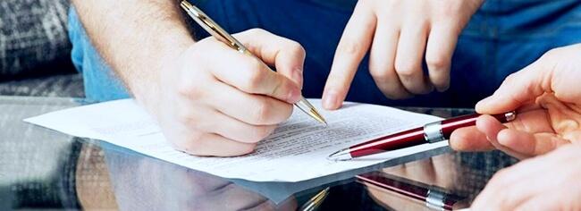Менеджер указывает клиенту, где поставить подпись в соглашении